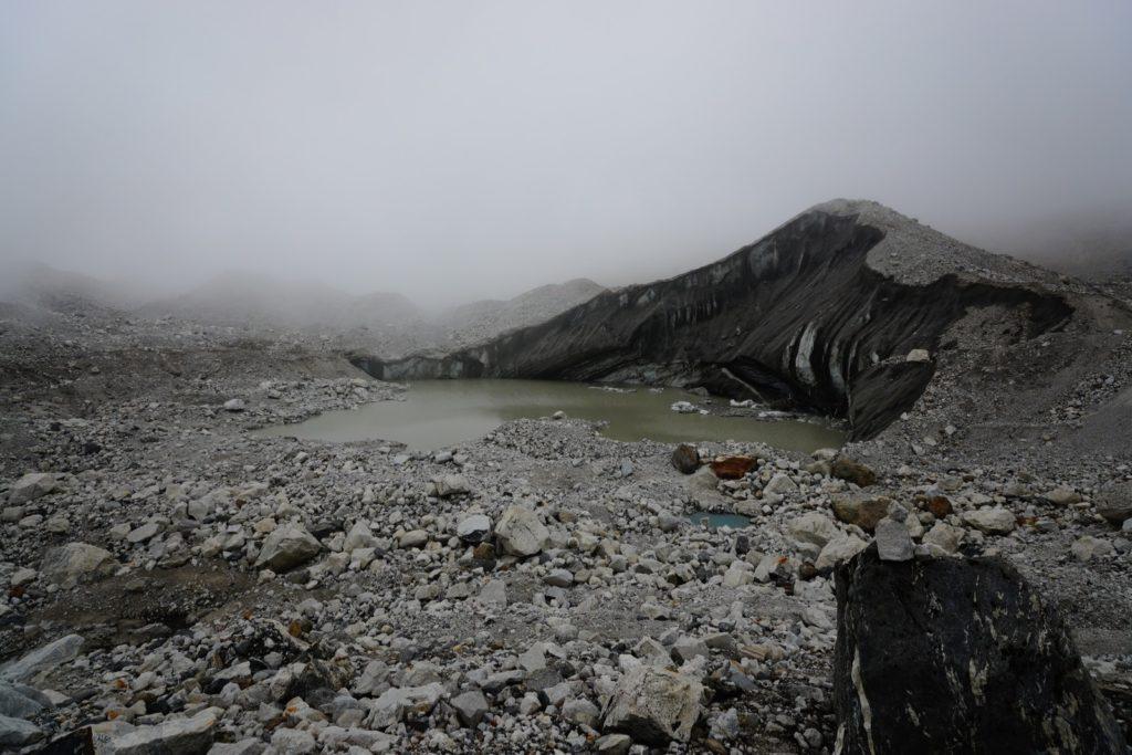 春天的冰川,融化中的冰塊和沙礫混合,構成一片荒涼。